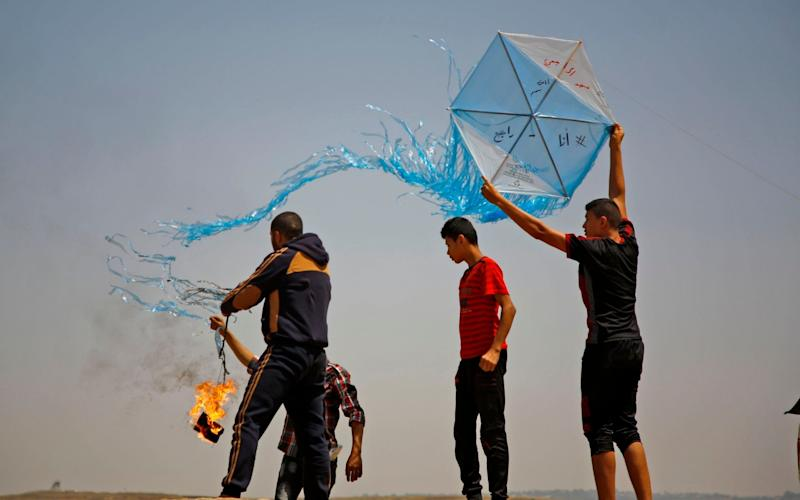 Palestinian protestors prepare to fly a kite loaded with an incendiary during a demonstration along the border with Israel east of Jabalia in the central Gaza Strip - AFP