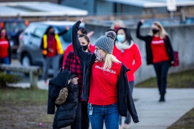 Teachers march at Ecole Woodward Hill Elementary School in Surrey on Tuesday in protest of how the school district and Fraser Health have handled COVID-19 safety.