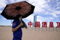 """A worker holds an umbrella near the Shenzhou-12 spacecraft covered on the launch pad with the Chinese characters reading """"China Jiuquan Satellite Launch Center"""" near Jiuquan on Wednesday, June 16, 2021. China plans to launch three astronauts onboard the Shenzhou-12 spacecraft, who will be the first crew members to live on China's new orbiting space station Tianhe, or Heavenly Harmony, from the Jiuquan Satellite Launch Center in northwest China. (AP Photo/Ng Han Guan)"""