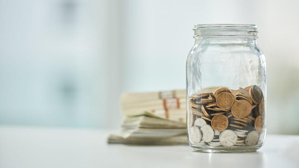 Full length shot of a jar of coins and wads of cash on a desk in an office.