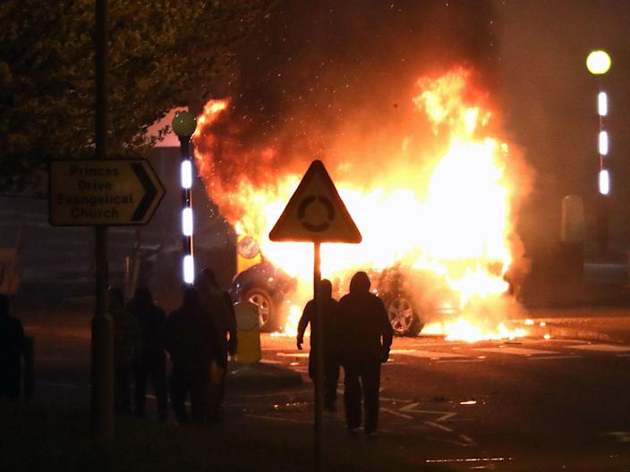 People walk past a burning car that was hijacked by loyalists at the Cloughfern roundabout in NewtownabbeyPeter Morrison/PA