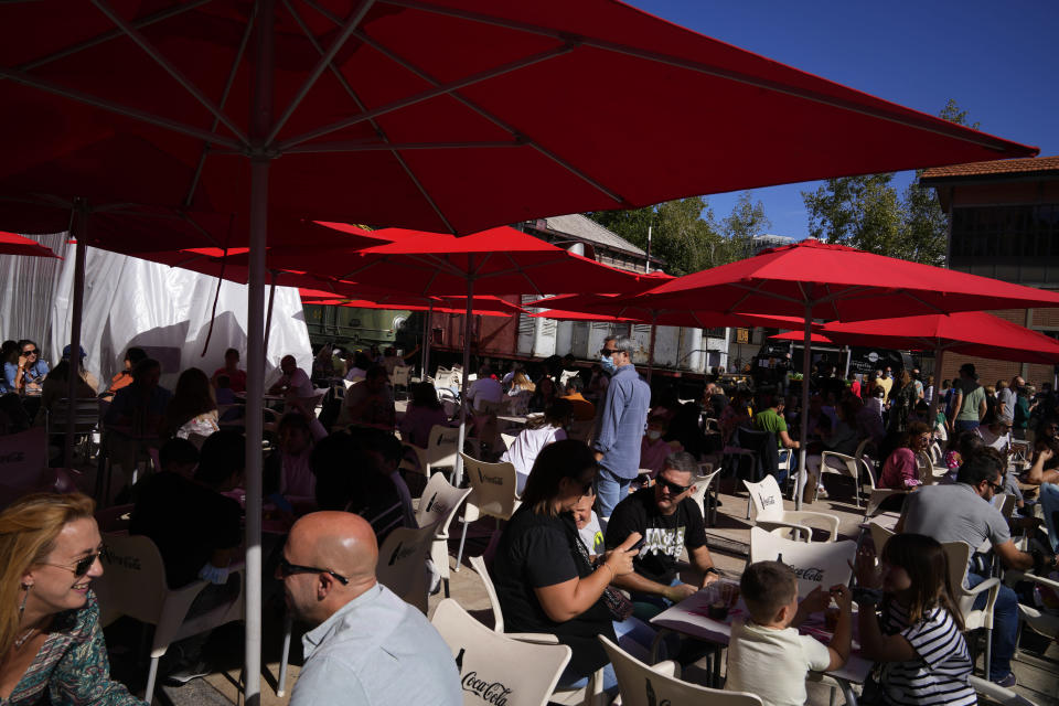 People enjoy drinks and snacks in an outside bar on the first weekend after Covid restrictions were eased in Madrid, Spain, Saturday, Oct. 9, 2021. (AP Photo/Paul White)