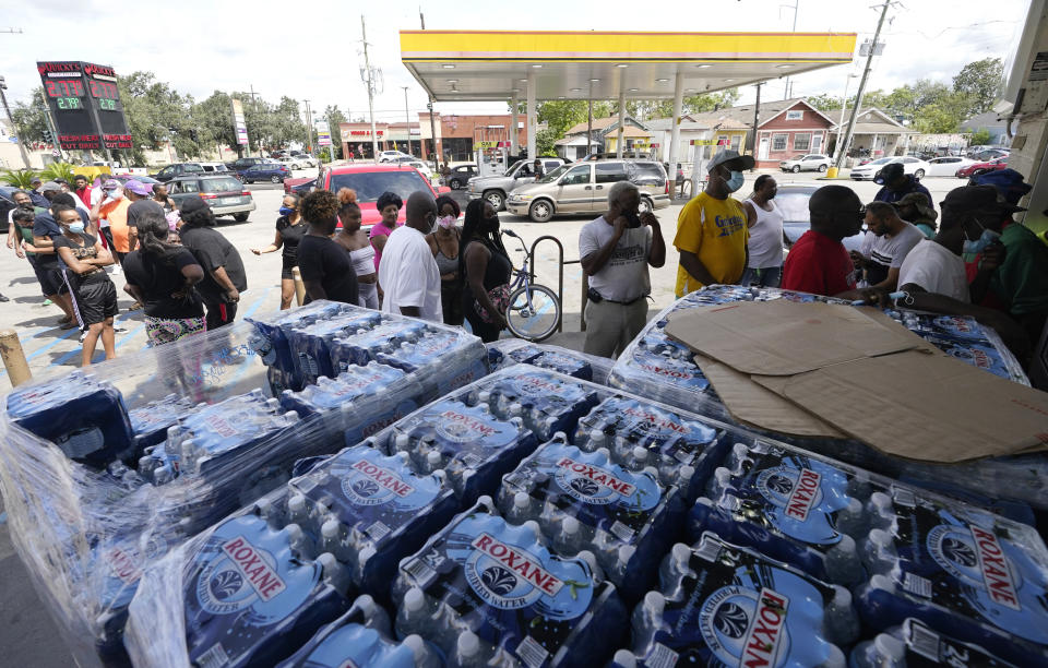 Customers stand in line to shop at a convenience store with no electricity in the aftermath of Hurricane Ida knocked out power in the area, Monday, Aug. 30, 2021, in New Orleans, La. (AP Photo/Eric Gay)