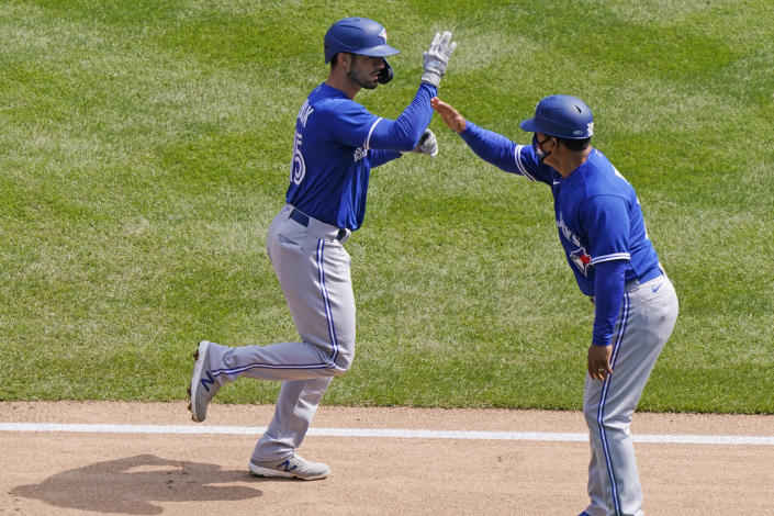 Toronto Blue Jays third base coach Luis Rivera congratulates Blue Jays Randal Grichuk, left, after Grichuk hit a two-run, home run during the second inning of a baseball game against the New York Yankees, Sunday, April 4, 2021, at Yankee Stadium in New York. (AP Photo/Kathy Willens)