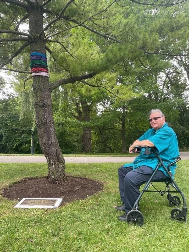 Indigenous elder Dan Smoke sits with the Tree of Peace planted July 11, 1991 in Ivey Park in London, Ont to commemorate the Oka Crisis in Quebec.  (Angela McInnes - image credit)