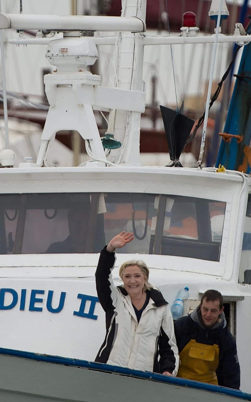 French presidential election candidate for the far-right Front National (FN) party Marine Le Pen (L) gestures aboard a fishing boat after meeting fishermen in the harbour of Le Grau-du-Roi, southern France, - Credit:  BERTRAND LANGLOIS/AFP