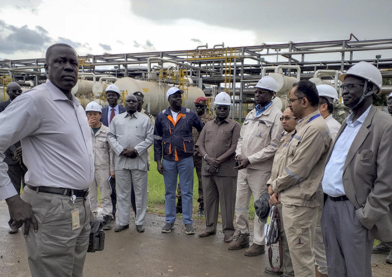 """In this photo taken Monday, Aug. 26, 2019, officials from the Chinese-led Dar Petroleum Operating Company and the Ministry of Petroleum, including Minister of Petroleum and Mining Awow Daniel Chuang, center wearing blue jeans, gather during a trip to the oil fields in Paloch, South Sudan. The oil industry in South Sudan has left a landscape pocked with hundreds of open waste pits with the water and soil contaminated with toxic chemicals and heavy metals, and accounts of """"alarming"""" birth defects, miscarriages and other health problems, according to four environmental reports obtained by The Associated Press. (AP Photo)"""