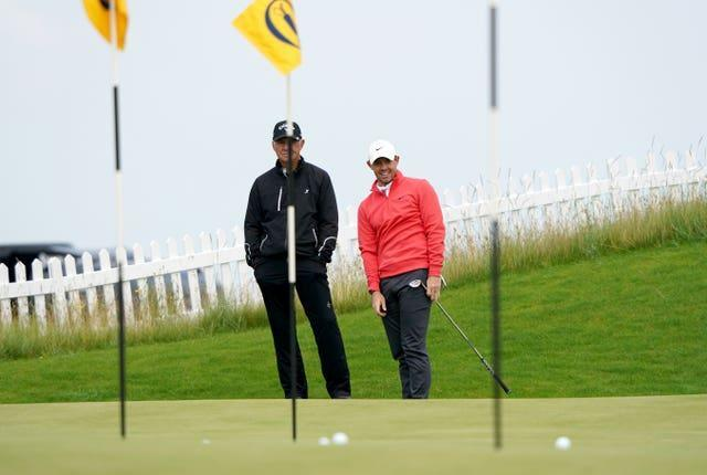 Rory McIlroy practises chipping watched by coach Pete Cowen