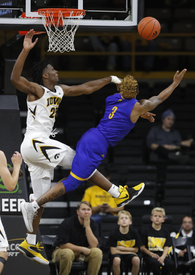 Iowa forward Tyler Cook, left, blocks a shot by UKMC guard Brandon McKissic during the second half of an NCAA college basketball game, Thursday, Nov. 8, 2018, in Iowa City, Iowa. (AP Photo/Charlie Neibergall)