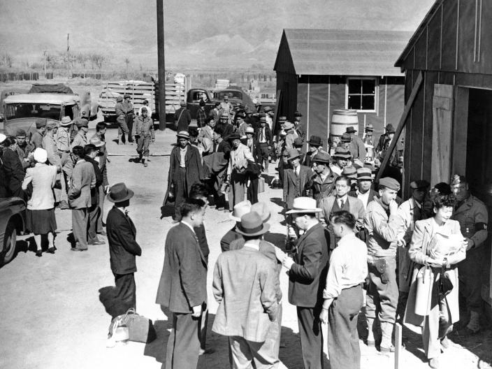 """FILE - This March 23, 1942, photo shows the first arrivals at the Japanese evacuee community established in Owens Valley in Manzanar, Calif. The auction of a series of sketches purportedly drawn by an artist at the Japanese internment camp has been canceled after groups protested it was offensive and immoral to profit off the misery of incarcerated people. The auction was halted Tuesday, April 6, 2021, by eBay hours before it was to conclude after company executives met with Japanese American groups who called the sale """"hurtful, and a degrading reminder of the mass roundup and incarceration."""" (AP Photo/File)"""