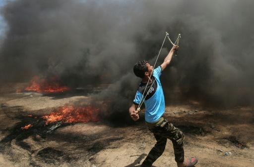 A Palestinian man uses a slingshot during clashes with Israeli forces along the border with the Gaza Strip on May 14, 2018