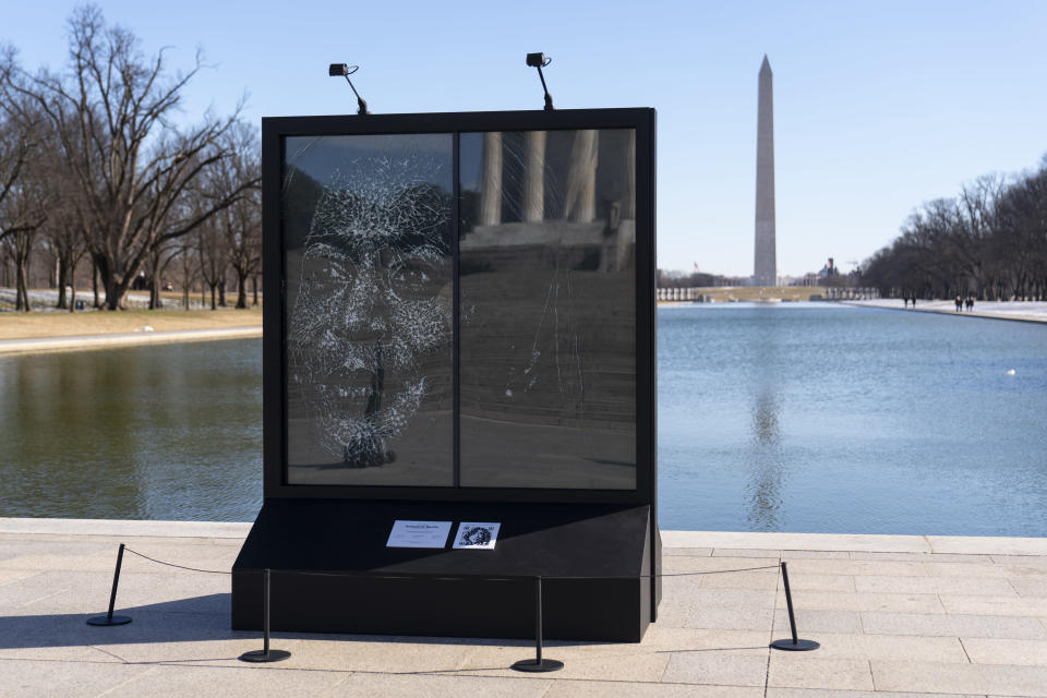 "The installation ""Vice President Kamala Harris Glass Ceiling Breaker"" is seen at the Lincoln Memorial in Washington, Wednesday, Feb. 4, 2021. Vice President Kamala Harris' barrier-breaking career has been memorialized in a portrait depicting her face emerging from the cracks in a massive sheet of glass. Using a photo of Harris that taken by photographer Celeste Sloman, artist Simon Berger lightly hammered on the slab of laminated glass to create the portrait of Harris. The Washington Monument is seen in the distance and the Lincoln Memorial is reflected. (AP Photo/Carolyn Kaster)"