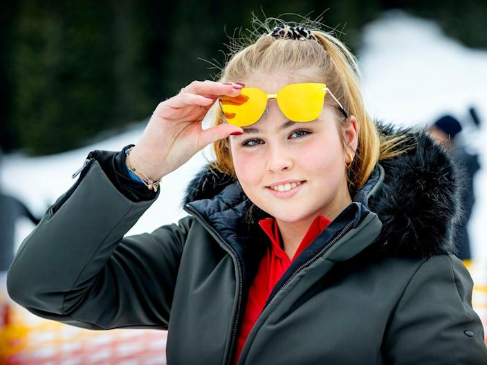 Princess Amalia of The Netherlands stands in a snowy backdrop and raises her sunglasses.