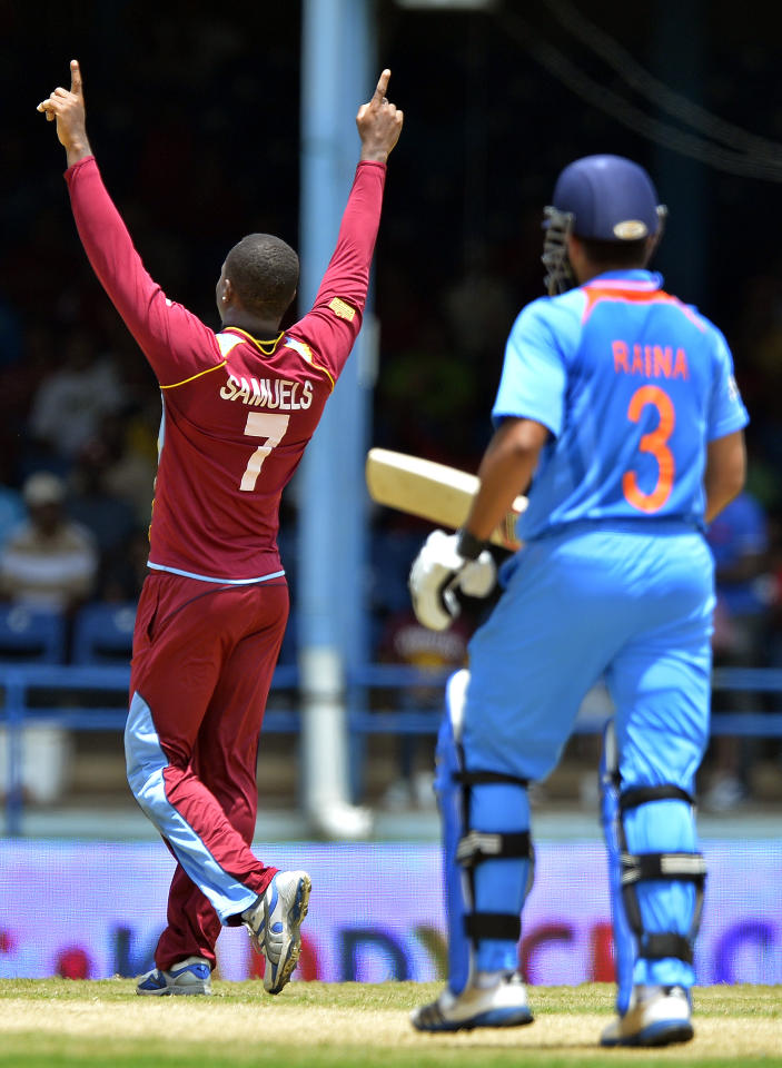 West Indies cricketer Marlon Samuels (L) celebrates dismissing Indian batsman Suresh Raina during the fourth match of the Tri-Nation series between India and West Indies at the Queen's Park Oval in Port of Spain on July 5, 2013. West Indies won the toss and elected to field. AFP PHOTO/Jewel Samad        (Photo credit should read JEWEL SAMAD/AFP/Getty Images)