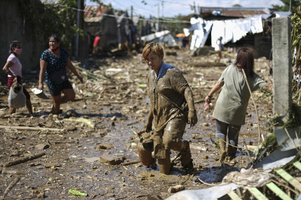 Gina Belchez carries a gas-stove through mud and debris in the typhoon-damaged Kasiglahan village in Rodriguez, Rizal province, Philippines on Friday, Nov. 13, 2020. Thick mud and debris coated many villages around the Philippine capital Friday after Typhoon Vamco caused extensive flooding that sent residents fleeing to their roofs and killing dozens of people. (AP Photo/Aaron Favila)