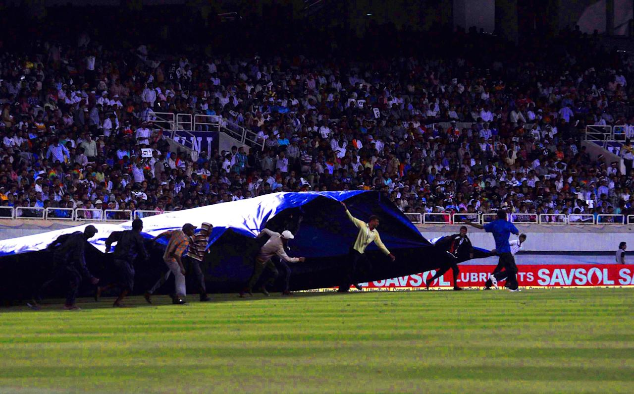 Ground staff run to cover-up the field as it starts raining during the 4th ODI between India and Australia at JSCA Stadium in Ranchi on Oct. 23, 2013. (Photo: IANS)