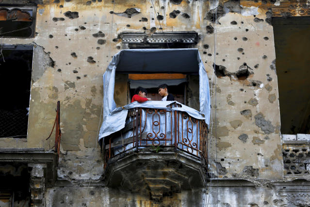 In this Nov. 12, 2018, photo, children stand on the balcony of their apartment building damaged during Lebanon's 1975-1990 civil war on a former Beirut frontline, Lebanon. Nearly 30 years after civil war guns fell silent, dozens of bullet-scarred, shell-pocked buildings are still standing _ testimony to a brutal conflict that raged for 15 years and took the lives of 150,000 people.(AP Photo/Hassan Ammar)