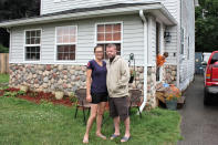 Crystal and Chris Martin stand outside their home, Sunday, July 19, 2020 in Burton, Mich., as one of their children looks on. The Martins, who had to defer some mortgage payments, are among millions of Americans who have struggled financially during the coronavirus pandemic. Crystal has been laid off since March from her job at a roller skating rink and Chris, an X-ray technician at a Flint hospital, was laid off, then took parental leave after the birth of a child this month. A new study by NORC at the University of Chicago finds that more than a quarter of Americans report losing income, investments and savings during the pandemic. (AP Photo/Tammy Webber)