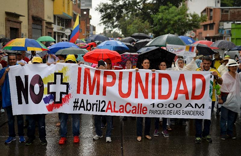 """People hold a banner reading """"No More impunity"""" during the """"No More"""" march against the government of President Juan Manuel Santos and the Revolutionary Armed Forces of Colombia (FARC) guerrillas in Cali (AFP Photo/Luis Robayo)"""