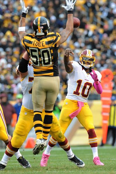Washington Redskins quarterback Robert Griffin III (10) tries to pass over leaping Pittsburgh Steelers inside linebacker Larry Foote (50) in the second quarter during an NFL football game on Sunday, Oct. 28, 2012, in Pittsburgh. (AP Photo/Don Wright)