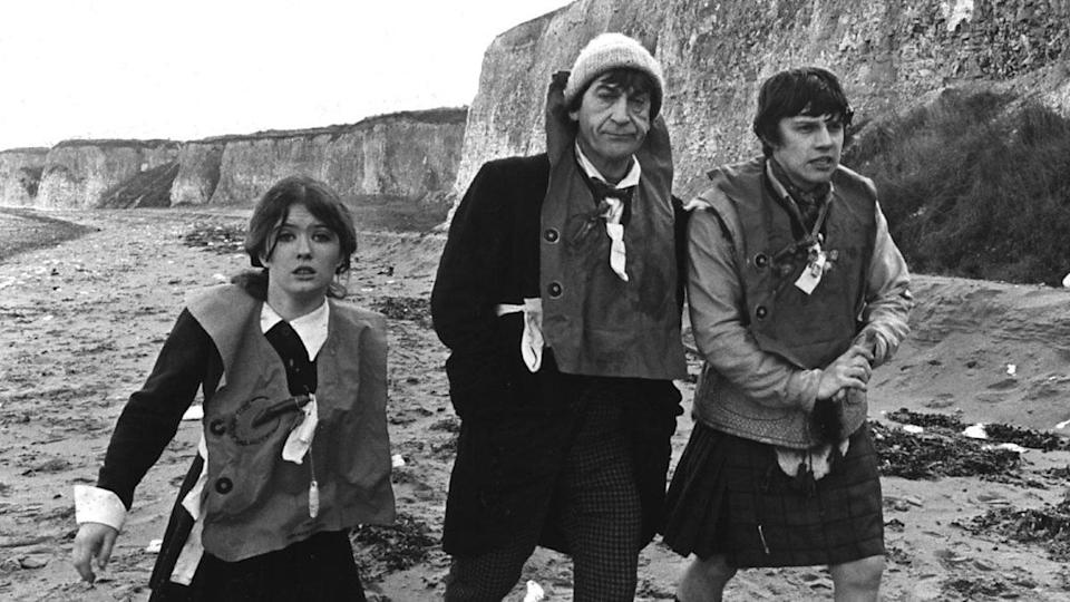 """Victoria, the Second Doctor, and Jamie trudge along a frigid beach in the Doctor Who story """"The Enemy of the World."""""""