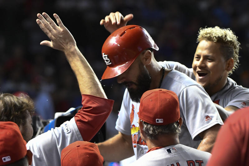St. Louis Cardinals' Matt Carpenter, center, celebrates in the dugout with relief pitcher Carlos Martinez, right, after he hit a home run against the Chicago Cubs during the tenth inning of a baseball game Thursday, Sept. 19, 2019, in Chicago. (AP Photo/Matt Marton)