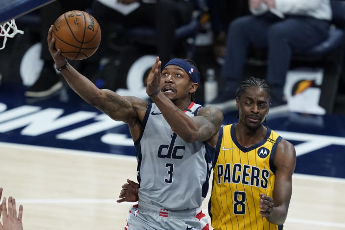 Washington Wizards' Bradley Beal (3) is fouled by Indiana Pacers' Justin Holiday (8) as he goes up for a shot during the first half of an NBA basketball game, Saturday, May 8, 2021, in Indianapolis. (AP Photo/Darron Cummings)
