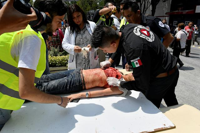<p>A woman is assisted after being injured during a quake in Mexico City on September 19, 2017.<br> A powerful earthquake shook Mexico City on Tuesday, causing panic among the megalopolis' 20 million inhabitants on the 32nd anniversary of a devastating 1985 quake. The US Geological Survey put the quake's magnitude at 7.1 while Mexico's Seismological Institute said it measured 6.8 on its scale. The institute said the quake's epicenter was seven kilometers west of Chiautla de Tapia, in the neighboring state of Puebla. (Photo: Omar Torres/AFP/Getty Images) </p>