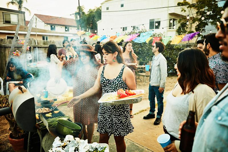 Women grilling food on barbecue during backyard party with friends