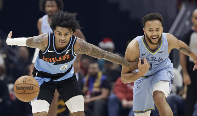 Cleveland Cavaliers' Kevin Porter Jr. (4) and Memphis Grizzlies' Kyle Anderson (1) battle for the ball in the first half of an NBA basketball game, Friday, Dec. 20, 2019, in Cleveland. (AP Photo/Tony Dejak)