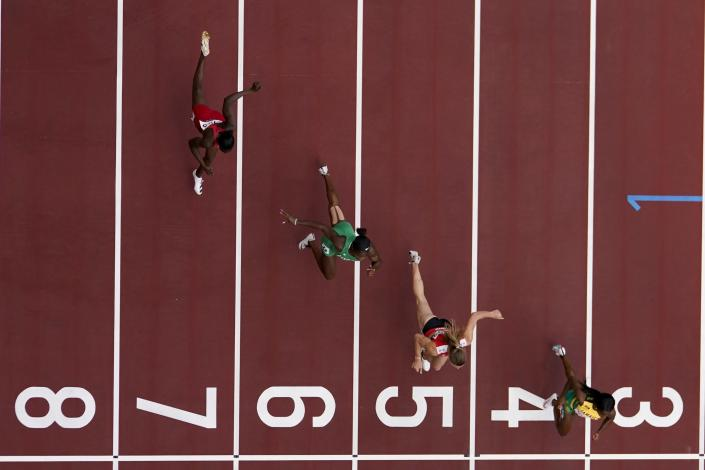 Shelly-Ann Fraser-Pryce, of Jamaica, Ajla Del Ponte, of Switzerland, Nzubechi Nwokocha, of Nigeria, and Gina Bass, of Gambia, compete during the first round of the women's 100-meter the 2020 Summer Olympics, Friday, July 30, 2021, in Tokyo. (AP Photo/Morry Gash)