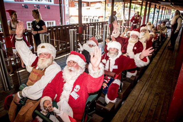 <p>Actors dressed as Santa Claus take a ride on a rollercoaster at the Bakken amusement park in Klampenborg north of Copenhagen, Denmark, on July 24, 2018, as they take part in the World Santa Congress, an annual two-day event held every summer in Copenhagen. (Photo: Mads Claus Rasmussen/Ritzau Scanpix/AFP/Getty Images) </p>