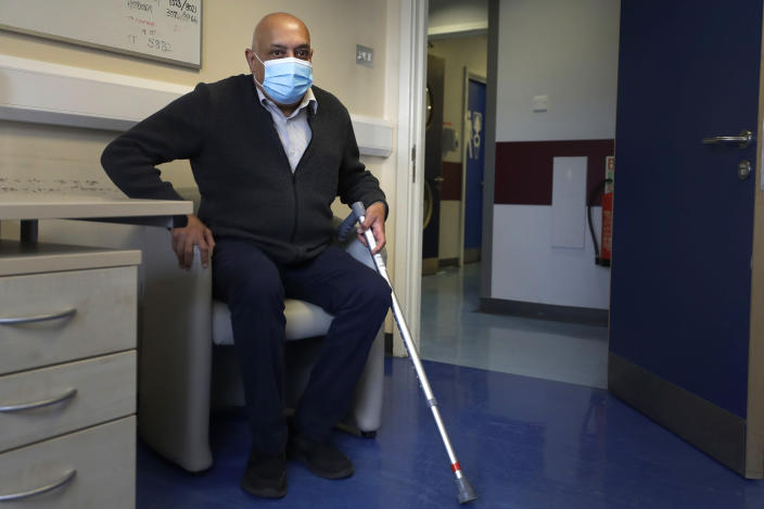 """Long COVID patient Rohit Patel takes a seat during a visit to the Long COVID Clinic at King George Hospital in Ilford, London, Tuesday, May 11, 2021. At King George Hospital, a clinic has been set up to help patients suffering months after they were infected with COVID-19. It's one of 83 """"long COVID"""" clinics in England where medics and patients are grappling with the enduring effects of the virus. (AP Photo/Kirsty Wigglesworth)"""
