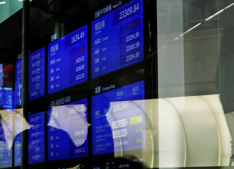 FILE PHOTO: People are reflected on a glass in front of a large screen showing stock prices at the Tokyo Stock Exchange after market opens in Tokyo