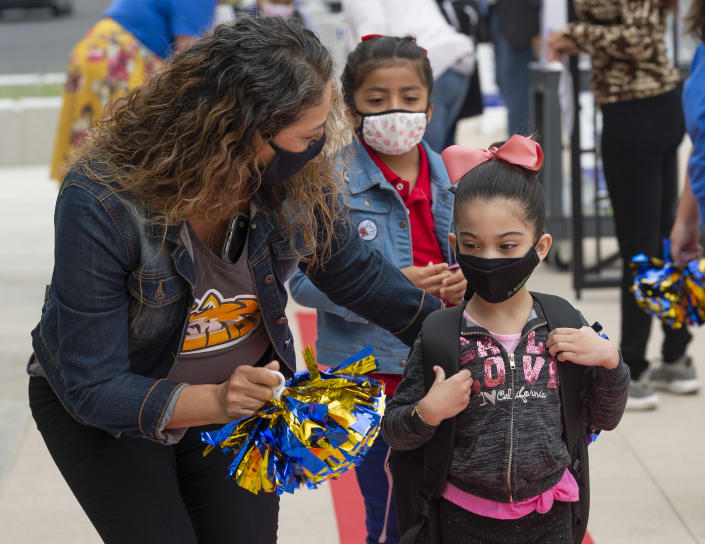 A student is welcomed back to school by school counselor Angelica Guzman at Sunkist Elementary School in Anaheim, CA on Monday, April 12, 2021. (Paul Bersebach/Orange County Register via Getty Images)