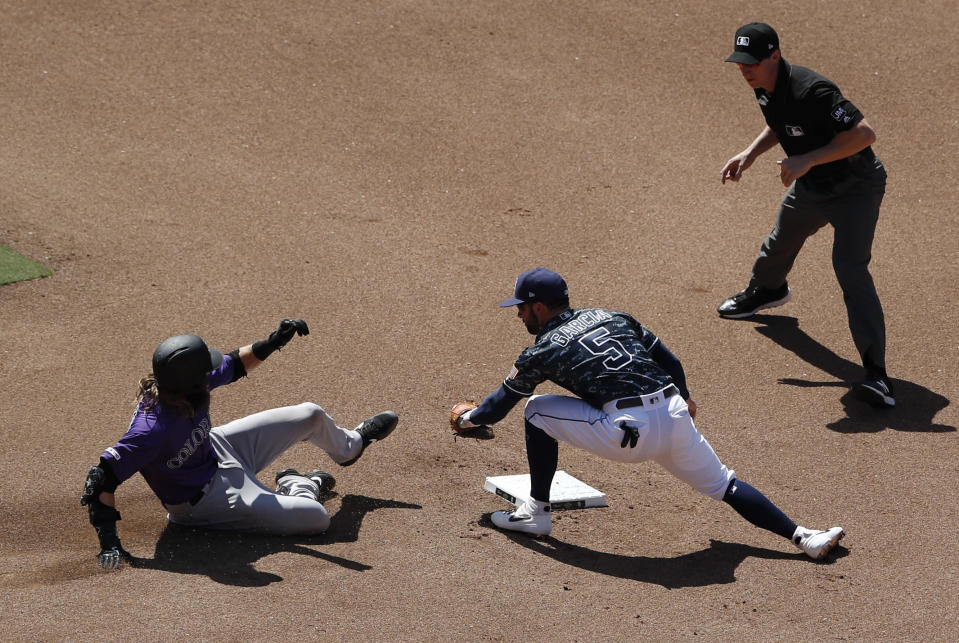 San Diego Padres second baseman Greg Garcia, center, tags out Colorado Rockies' Charlie Blackmon, left, at second during the fourth inning of a baseball game Sunday, Sept. 8, 2019, in San Diego. (AP Photo/Gregory Bull)