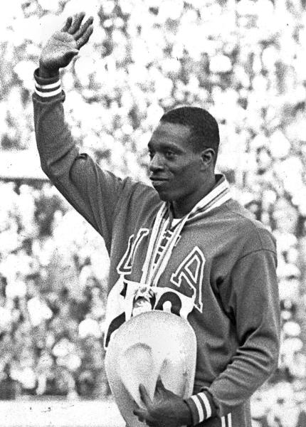 FILE - In an Oct. 15, 1964, file photo, United States' Bob Hayes waves to the crowd from the victory stand after winning the men's 100-meter dash finals at the 1964 Tokyo Summer Olympics. Hayes' gold medal in the 100 meters earned him the designation of the world's fastest human and provided him the opportunity to become the first Olympic champion to make it big in professional football as a wide receiver for nine years with the Dallas Cowboys, and a two-time All-Pro. With the 2012 London Summer Olympics over, The Associated Press takes a look at six teams that could look to copy Hayes' success by pursuing Jamaican runner Usain Bolt. (AP Photo, File)