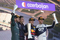 First place, Red Bull driver Sergio Perez of Mexico, second right, stands on the podium with second place, Aston Martin driver Sebastian Vettel of Germany, left, and third place, AlphaTauri driver Pierre Gasly of France, right, during the Formula One Grand Prix at the Baku Formula One city circuit in Baku, Azerbaijan, Sunday, June 6, 2021. (AP Photo/Darko Vojinovic)