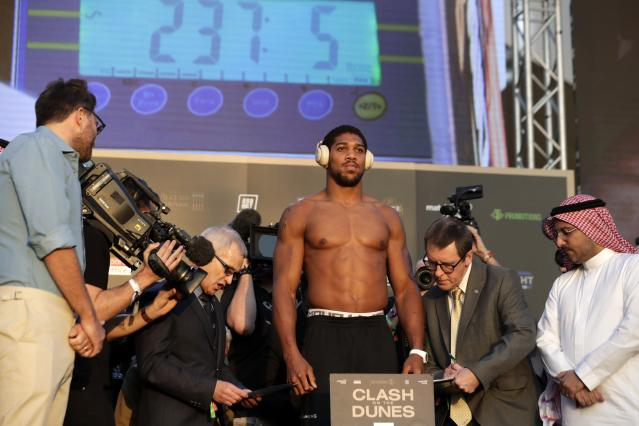 "Officials check the weight of the British boxer Anthony Joshua during a weigh-in at Faisaliah Center, in Riyadh, Saudi Arabia, Friday, Dec. 6, 2019. The first ever heavyweight title fight in the Middle East, has been called the ""Clash on the Dunes."" Will take place at the Diriyah Arena on Saturday. (AP Photo/Hassan Ammar)"