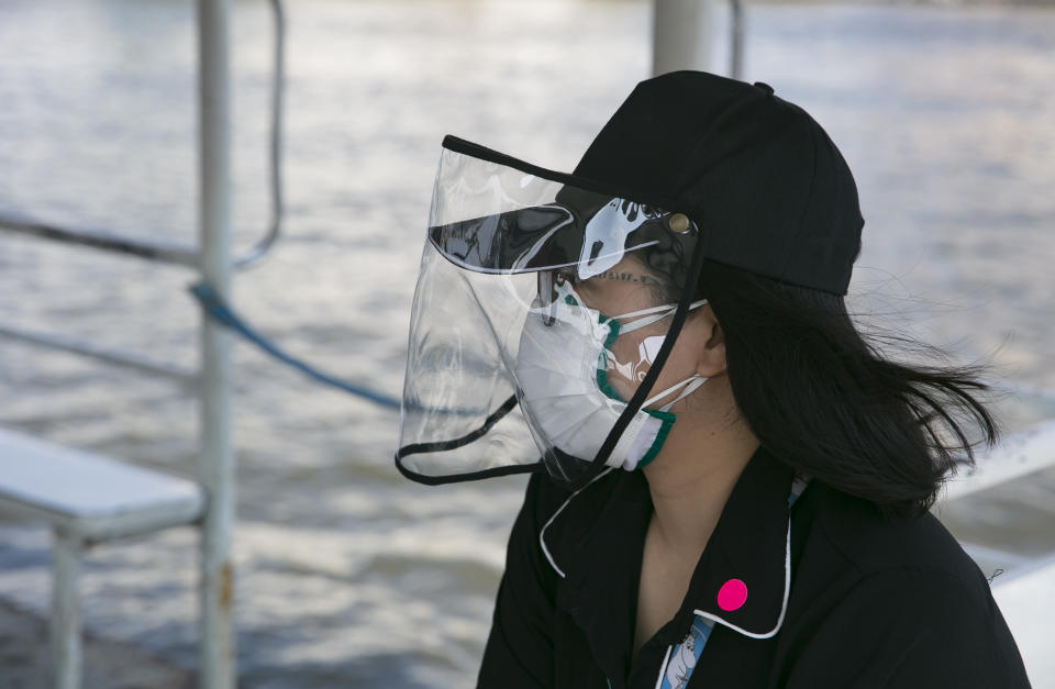 BANGKOK, THAILAND - MARCH 27:  A woman wears a mask on a commuter boat as Thailand imposed a state of emergency to combat the spread of the coronavirus (COVID-19) on March 27, 2020 in Bangkok, Thailand.  It is now compulsory to wear a mask while using public transportation. Thailand's Department of Disease Control has confirmed 91 new cases of the virus and are advising people to stay home.  (Photo by Allison Joyce/Getty Images)