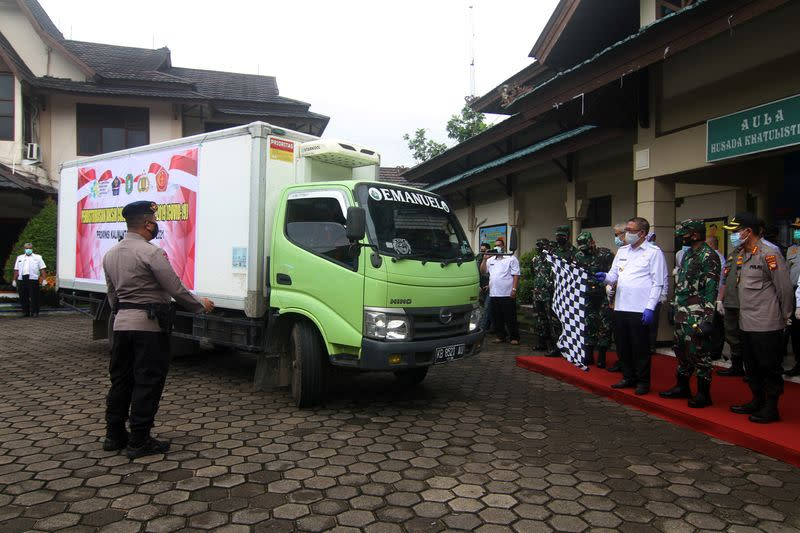 West Kalimantan Governor Sutarmidji holds a flag during a ceremony to start Sinovac's COVID-19 vaccine distribution in Pontianak