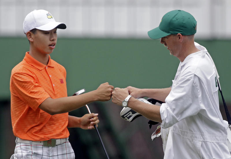 Amateur Guan Tianlang, of China, touches fists with his caddie Brian Tam after putting on the third hole during the second round of the Masters golf tournament Friday, April 12, 2013, in Augusta, Ga. (AP Photo/David Goldman)