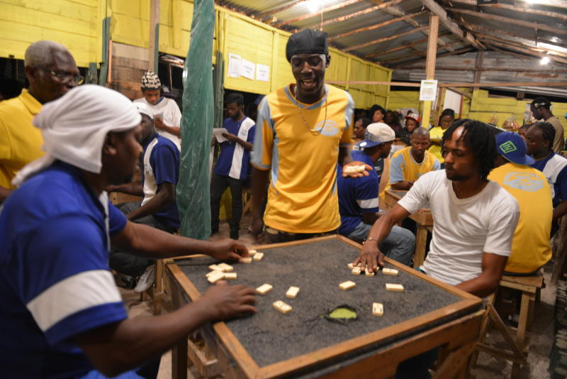 In this Nov. 3, 2013 photo, a domino player celebrates winning a competitive match in Constitution Hill, a rural mountain town on the outskirts of Kingston, Jamaica. In Jamaica, it's almost an obsession for many players, who can be seen each evening slamming domino tiles on card tables on street corners or outside rum bars in cities and rural towns. The government officially recognizes competitive dominoes as a sport. (AP Photo/David McFadden)