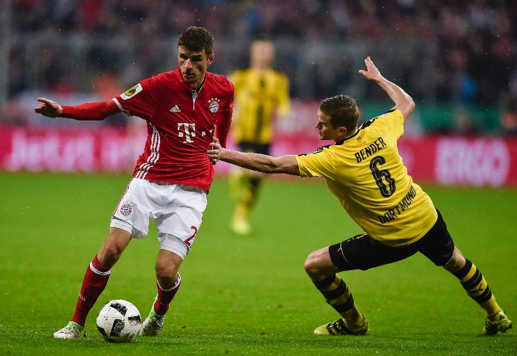 Bayern Munich's striker Thomas Mueller (L) and Dortmund's midfielder Sven Bender vie for the ball during the German Cup DFB Pokal semifinal football match April 26, 2017 (AFP Photo/GUENTER SCHIFFMANN)