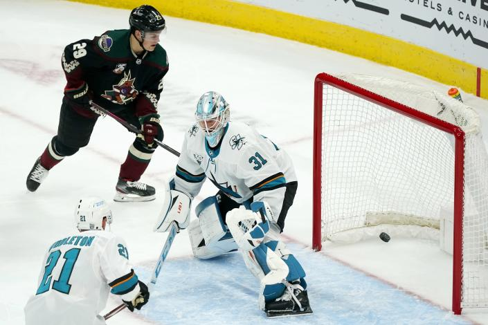 San Jose Sharks goaltender Martin Jones (31) gives up a goal to Arizona Coyotes' Phil Kessel as Sharks defenseman Jacob Middleton (21) and Coyotes center Barrett Hayton (29) look on during the first period of an NHL hockey game Saturday, Jan. 16, 2021, in Glendale, Ariz. (AP Photo/Ross D. Franklin)