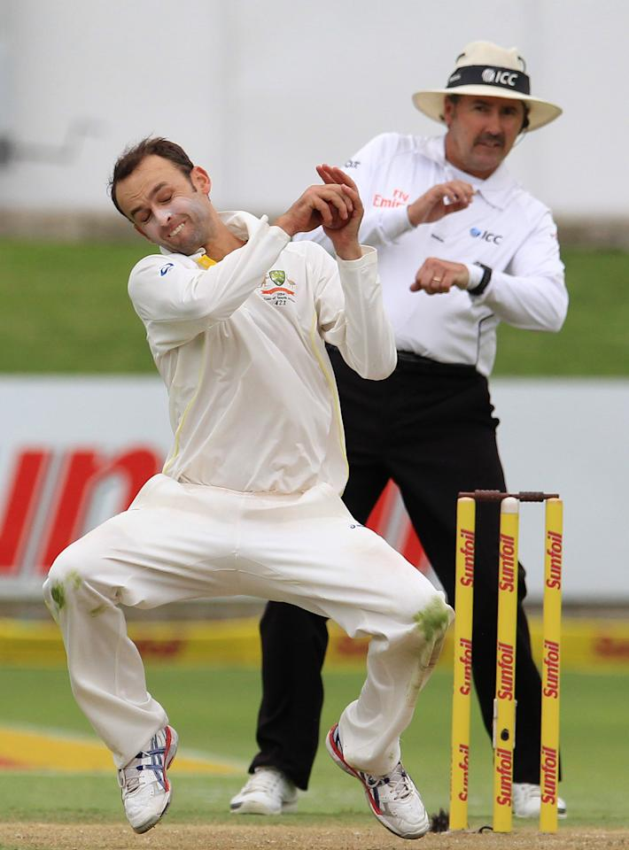 Australia's bowler Nathan Lyon, left, fields from his own bowling as umpire Richard Illingworth of England, right, reacts on the first day of their 2nd cricket test match against South Africa at St George's Park in Port Elizabeth, South Africa, Thursday, Feb. 20, 2014. (AP Photo/ Themba Hadebe)