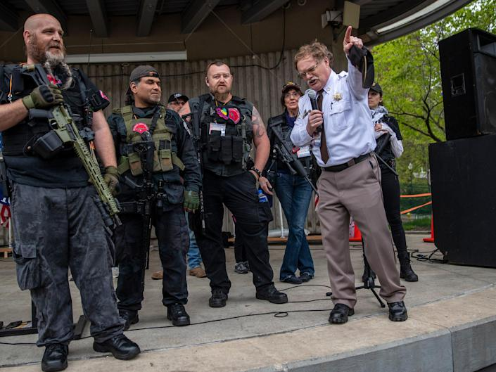 """Barry County Sheriff Dar Leaf, front right, speaks next to members of the Michigan Liberty Militia during the """"American Patriot Rally-Sheriffs speak out"""" event at Rosa Parks Circle in downtown Grand Rapids, Mich., Monday, 18 May, 2020 ((MLive/Grand Rapids Press via the Associated Press))"""