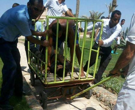 Workers and security detain the man who stabbed tourists during an attack at the Zahabia hotel resort in Hurghada