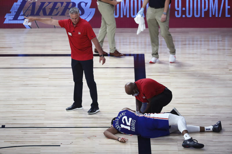 Brett Brown watches as Tobias Harris, on the floor, is attended to after a scary fall.