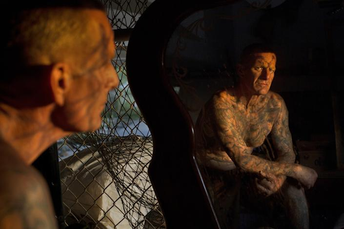 "Kenneth Colato looks in a mirror in his home under a bridge along the L.A. River in the Sepulveda Basin in April 2017. <span class=""copyright"">(Ivan Kashinsky / For The Times)</span>"